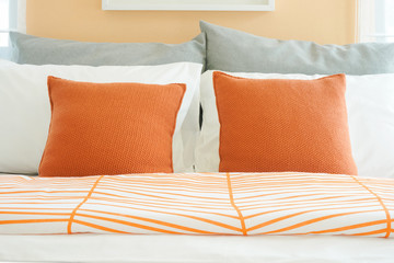Closeup roll of pillows on bed, orange, white and gray  colour