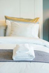 Clean white towels setting on bed in bedroom