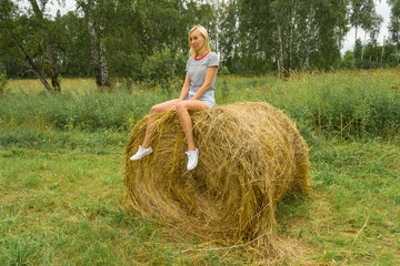 A beautiful blonde girl smiles and holds a bunch of grass between her legs and sits on a large round stack of dry hay collected smiling and on a summer or autumn afternoon