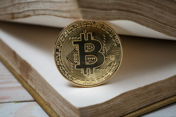 Golden bitcoin on open book electronic or digital money