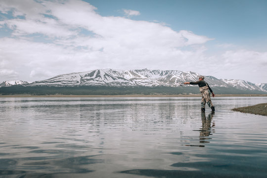 The guy fishing on the shore of a mountain lake . Reflection of mountains in water