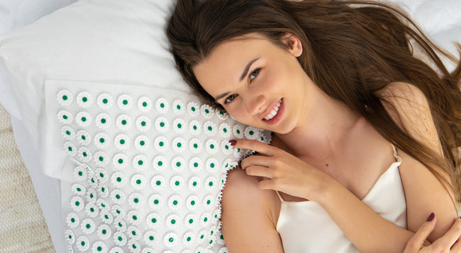young woman with acupuncture massage mat
