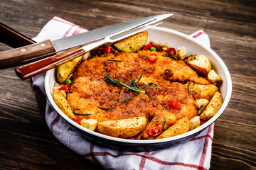 Fried pork chop, baked potatoes and vegetables in pan on wooden background