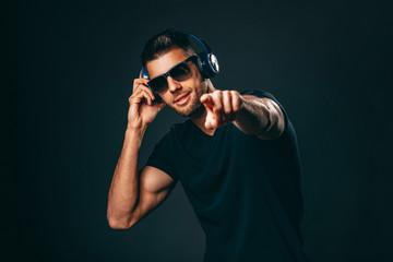 Handsome man with headphones in studio on dark background