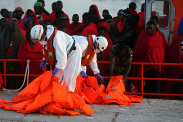 Rescuers carry the life vests of migrants intercepted off the coast in the Mediterranean Sea after arriving on a rescue boat at the port of Malaga