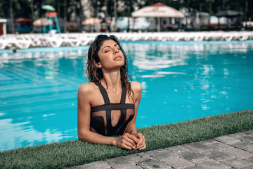 Fashion photo attractive slim woman with long dark hair in an elegant striped body swimsuit relaxing in a pool at a tropical resort. Wet girl posing in the water. Young woman coming out of the pool.