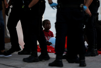 A migrant child looks at Spanish police officers after arriving on a rescue boat at the port of Malaga
