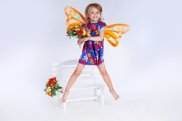 Girl in butterfly costume. Child posing in studio. Girl with butterfly wings. Baby and flowers. Fly of butterfly..