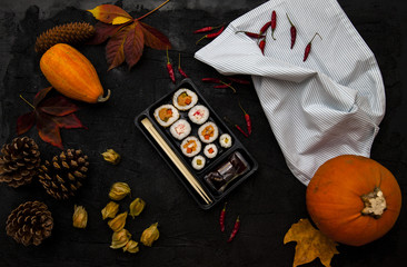 Still life with products on a black background: a set of sushi, a towel, peppers, physalis, pumpkins, cones, fallen yellow leaves