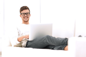 successful young male freelancer working on laptop at home.