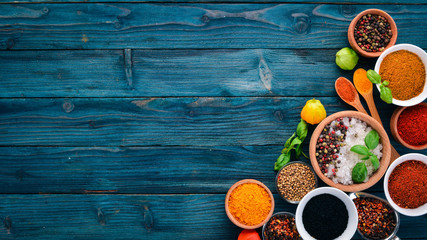 Fototapeta Spices and herbs on a blue wooden table. Basil, pepper, saffron, spices. Indian traditional cuisine. Top view. Free copy space. obraz