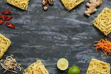 Ingredients for asian dish. Dried asian noodles with lime, nuts, cilantro and vegetables on wooden background