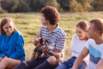 Outdoor shot of pleased cheerful friends or companions being in good mood, sing songs from their childhood, remember positive moments during their friendship, spend free time in meadow outside