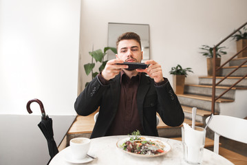 Business man photographing food on the smartphone. Man in a suit sitting in a light cozy restaurant and takes a photo of food on a smartphone.