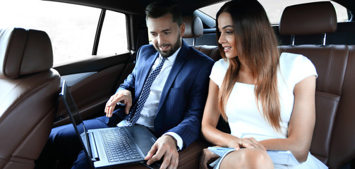 Young business team sitting on the backseat of a taxi