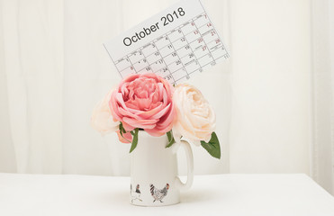 Composition in pastel colors on a white background. Calendar October 2018 is on top of a bouquet of flowers in a vase with funny chickens. It is on a white table in a room with white curtains.