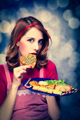 Redhead women with cookies on bokeh background