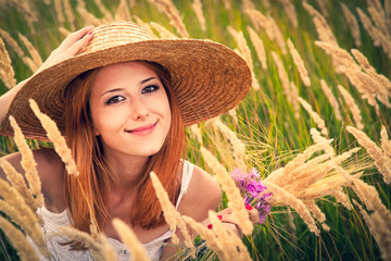 Redhead girl in hat sitting in grass. Autumn season time