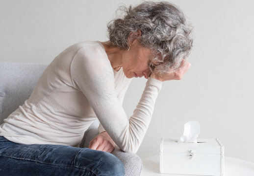 Close up side view of middle aged woman with grey hair holding head and looking down at tissue box - grief concept  (selective focus)