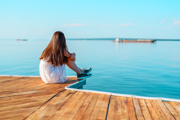Lonely young girl in white dress sitting on the pier hugging her knees looking into the horizon, loneliness, parting, waiting, autism, sadness, copy space