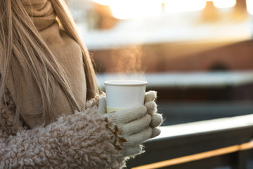Female hands in white mittens holding steaming white cup of hot coffee or tea in cold winter sunny day, closeup.Winter time concept.Bask in the cold