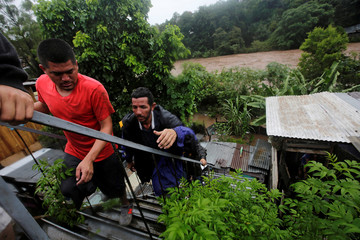 Residents climb stairs nearby the Choluteca river following heavy rains in Tegucigalpa