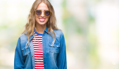 Beautiful young blonde woman wearing sunglasses over isolated background with a happy and cool smile on face. Lucky person.