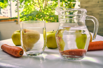 Jug and glass of water with fruits from behind