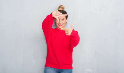 Young adult woman over grey grunge wall wearing winter outfit smiling making frame with hands and fingers with happy face. Creativity and photography concept.