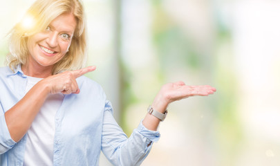 Middle age blonde woman over isolated background amazed and smiling to the camera while presenting with hand and pointing with finger.