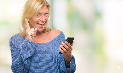 Middle age blonde woman sending message using smartphone over isolated background surprised with an idea or question pointing finger with happy face, number one