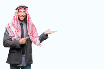 Young handsome arabian man with long hair wearing keffiyeh over isolated background amazed and smiling to the camera while presenting with hand and pointing with finger.