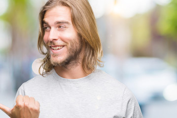 Young handsome man with long hair over isolated background smiling with happy face looking and pointing to the side with thumb up.