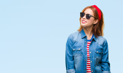 Young beautiful woman over isolated background wearing sunglasses looking away to side with smile on face, natural expression. Laughing confident.