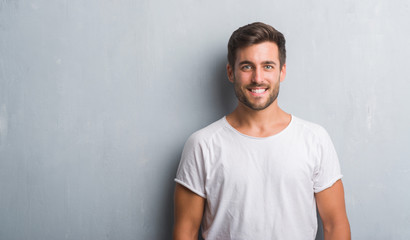 Handsome young man over grey grunge wall with a happy and cool smile on face. Lucky person.