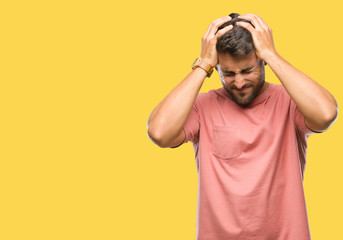 Young handsome man over isolated background suffering from headache desperate and stressed because pain and migraine. Hands on head.