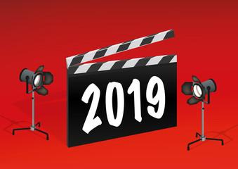 Carte de vœux 2019 célébrant le cinéma, avec un clap de film éclairé par deux projecteurs