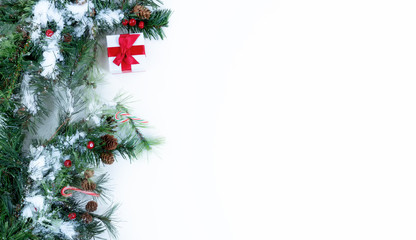 Snow covered Christmas tree branches and decorations on left side of solid white background