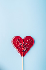 Heart lollipop candy on a blue background