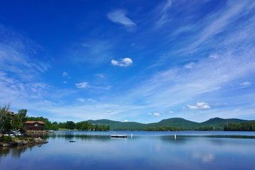 Adirondack Park, New York, USA: View of Blue Mountain in the distance from the shore of Blue Mountain Lake, with while clouds in a deep blue sky above.