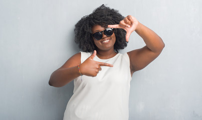 Young african american plus size woman over grey grunge wall wearing fashion sunglasses smiling making frame with hands and fingers with happy face. Creativity and photography concept.