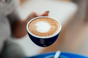 Close up of woman hands holding blue cup of coffee.