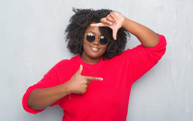 Young african american plus size woman over grey grunge wall wearing retro sunglasses smiling making frame with hands and fingers with happy face. Creativity and photography concept.