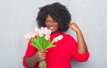 Young african american woman over grey grunge wall holding pink flowers bouquet screaming proud and celebrating victory and success very excited, cheering emotion