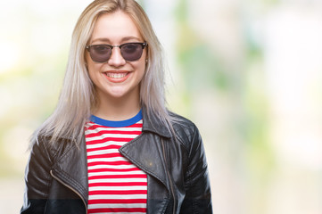Young blonde woman wearing fashion jacket and sunglasses over isolated background with a happy and cool smile on face. Lucky person.