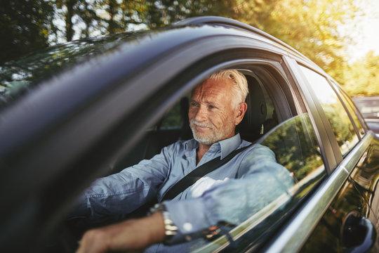 Smiling senior man driving along a country road