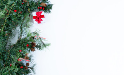 Christmas tree branches and decorations on left side of solid white background