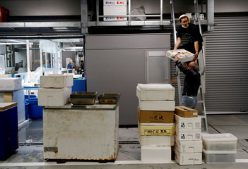 Men move boxes as they install a new store at a building of Toyosu fish market during a relocation from Tsukiji to Toyosu in Tokyo