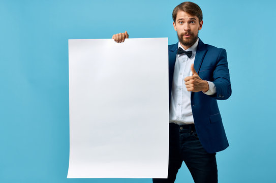 business man in a suit holds in his hand a white sheet of paper poster