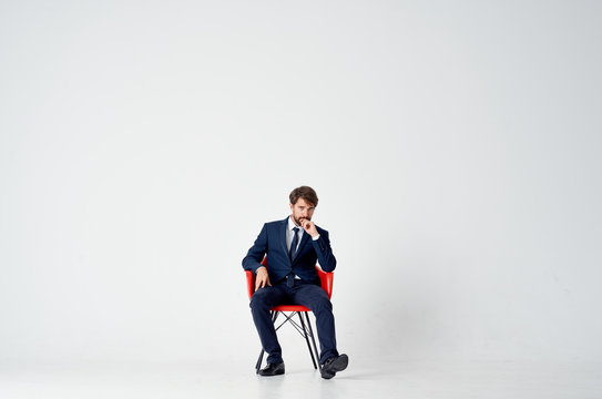man in a suit sitting on a red chair